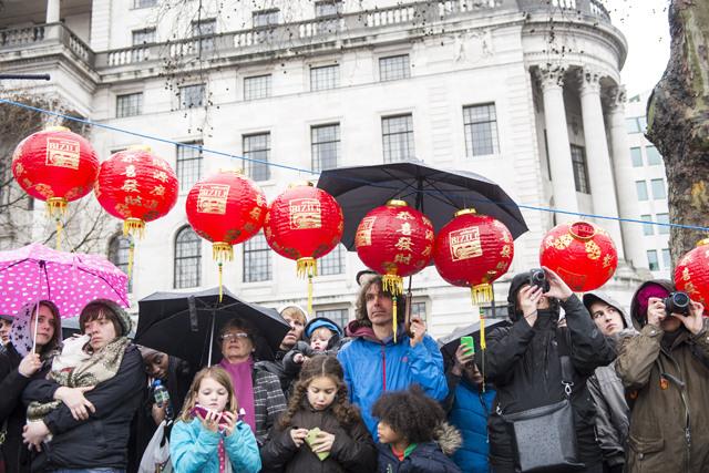People watching the Trafalgar Square show under the rain