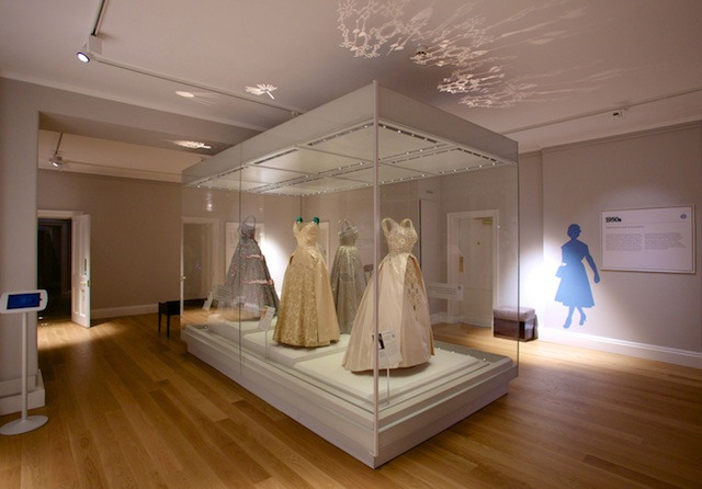 A case of beautiful dresses worn by HM The Queen opens the new Fashion Rules show at Kensington Palace