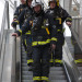 Firefighters travel down an escalator