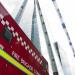 A police officer walks beside London Fire Brigade's Command Unit